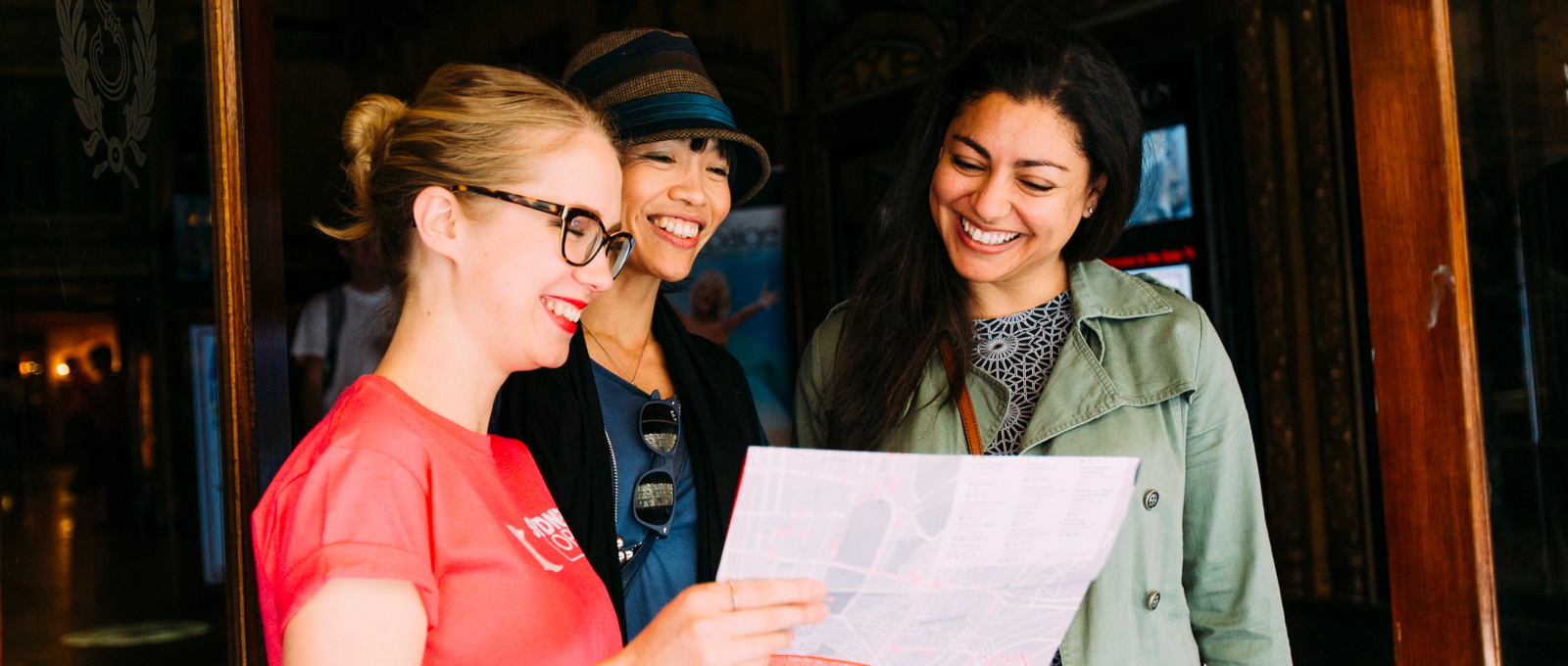 <p>Sydney Open volunteer speaking with visitors at the entrance to the State Theatre.&nbsp;Photo &copy; Haley Richardson for Sydney Living Museums</p>