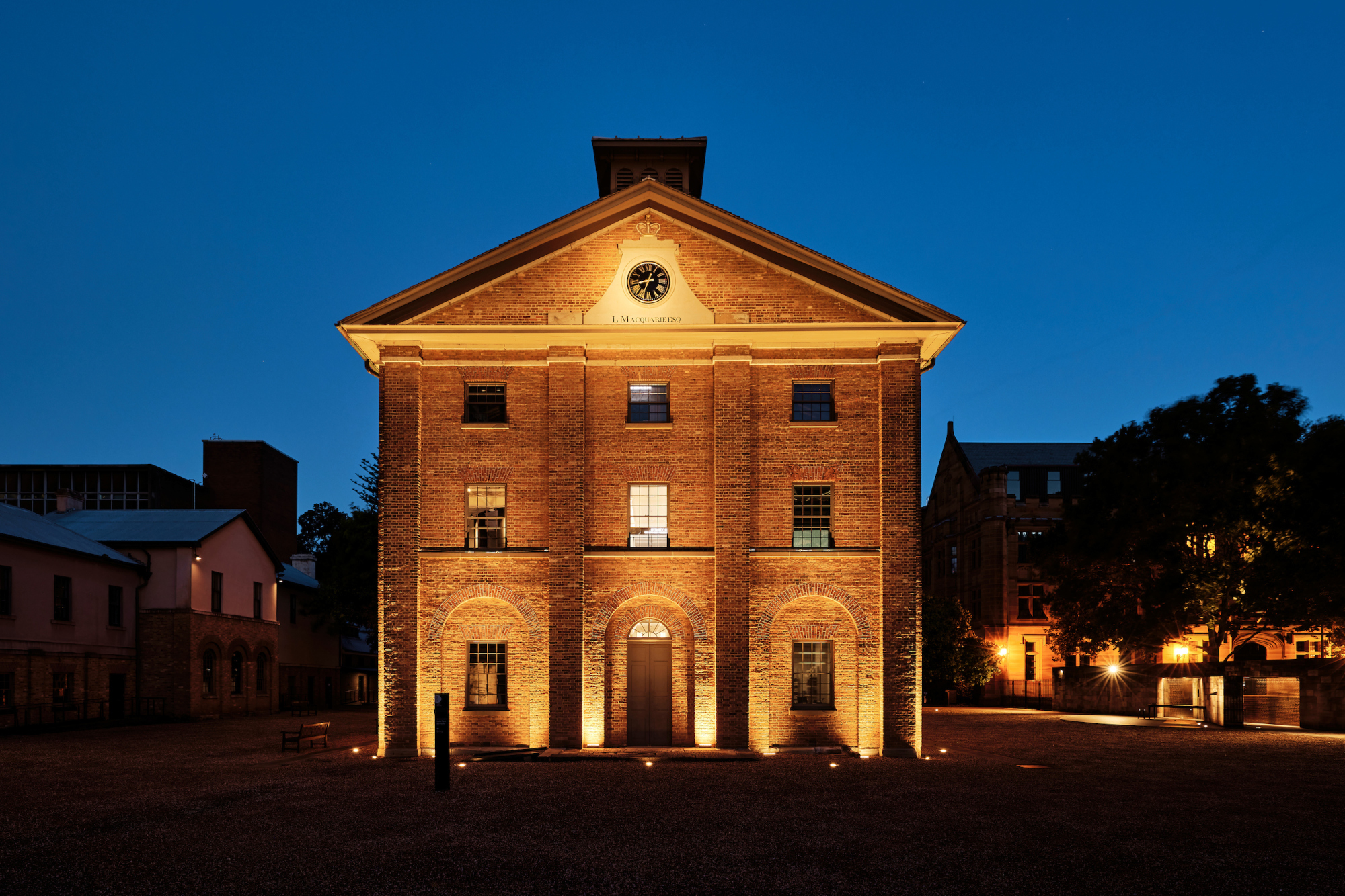 Facade of two storey brick colonial era building with lighting.