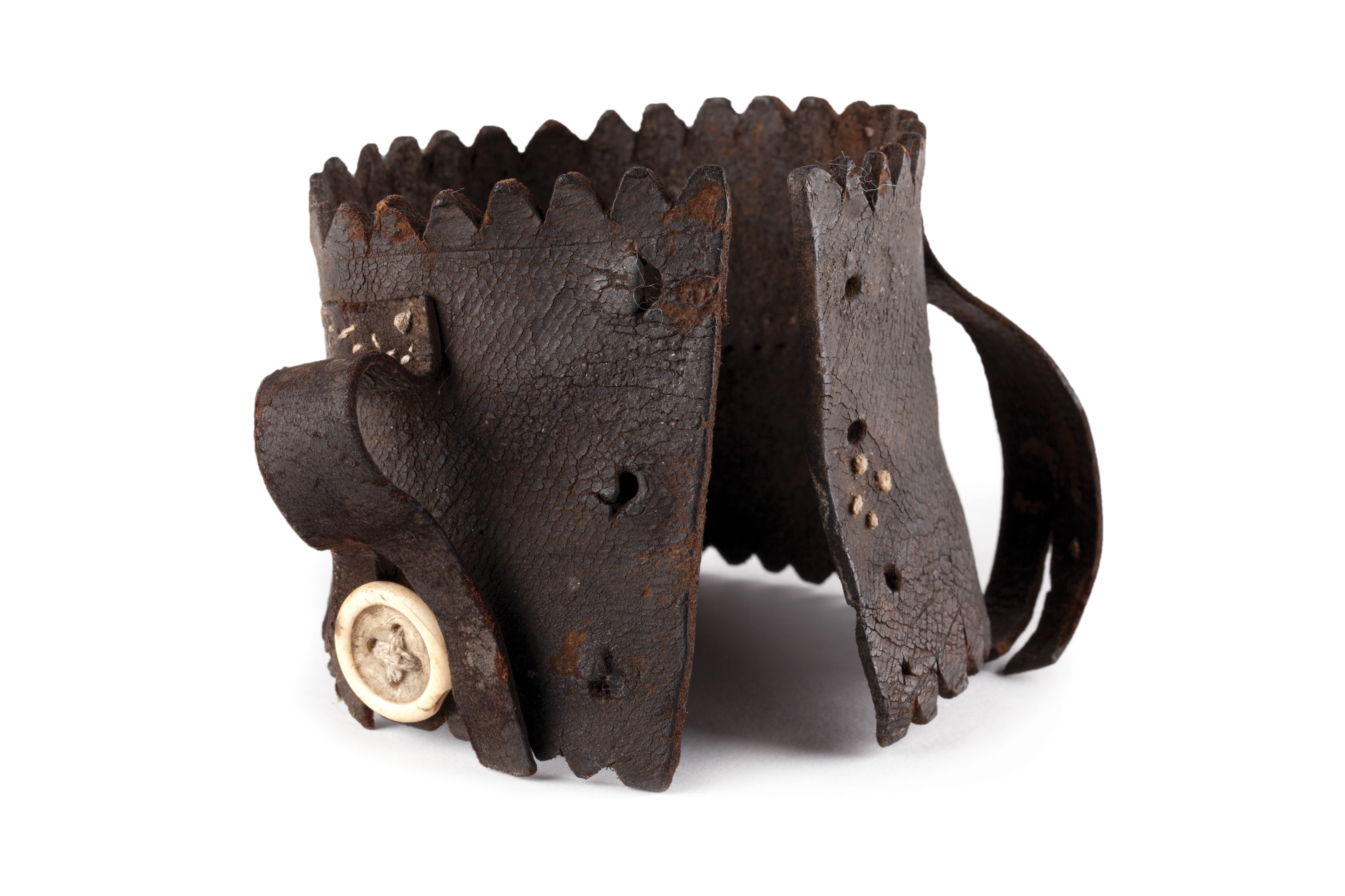 Brown leather hand sewn and shaped object with buttons and ties.