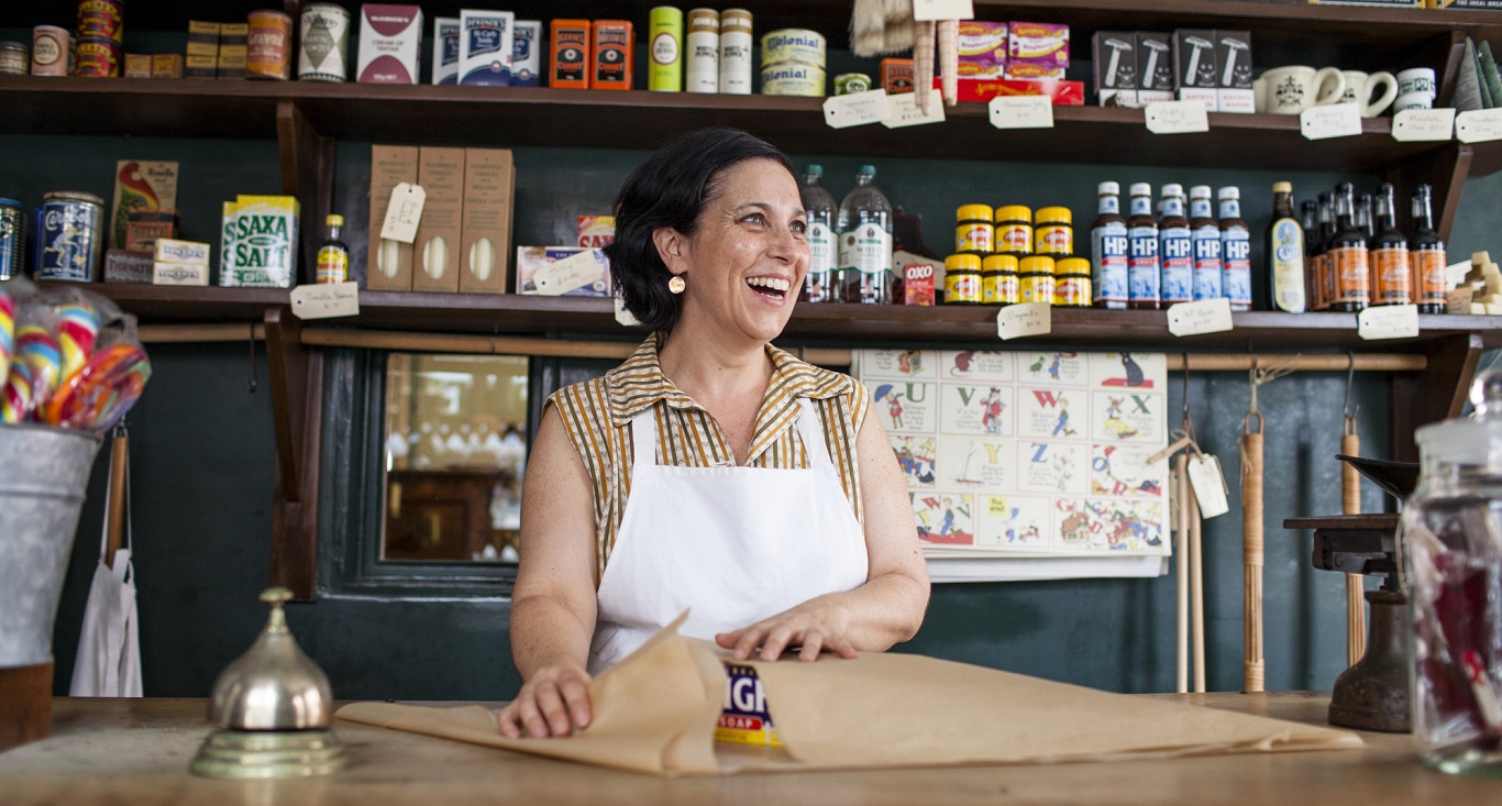 Woman behind old-fashioned shop counter.