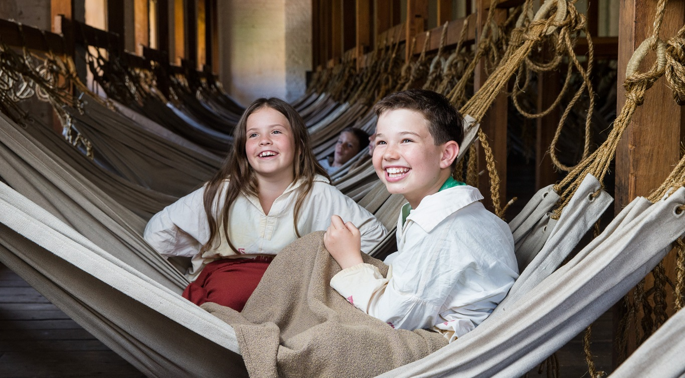 Two children dressed as convicts in hammock room.