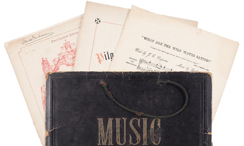 Sheet music sticking out of top of leather bound book with the word Music on its cover.