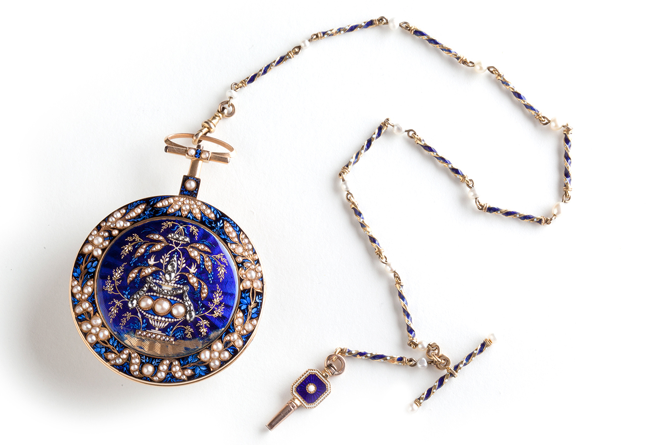 Ornately decorated blue pocket watch on a chain.