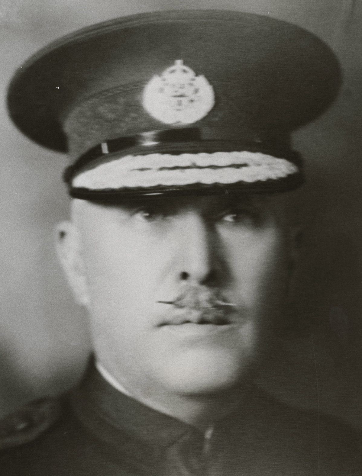 Mustachioed man with police hat on.