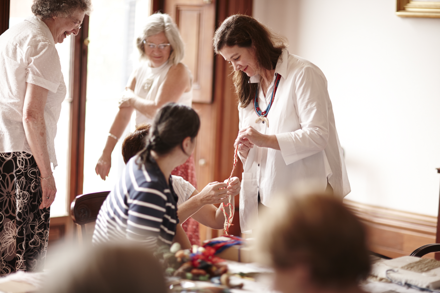 Woman in white standing with two other women at dining table assisting two seated women with threads.