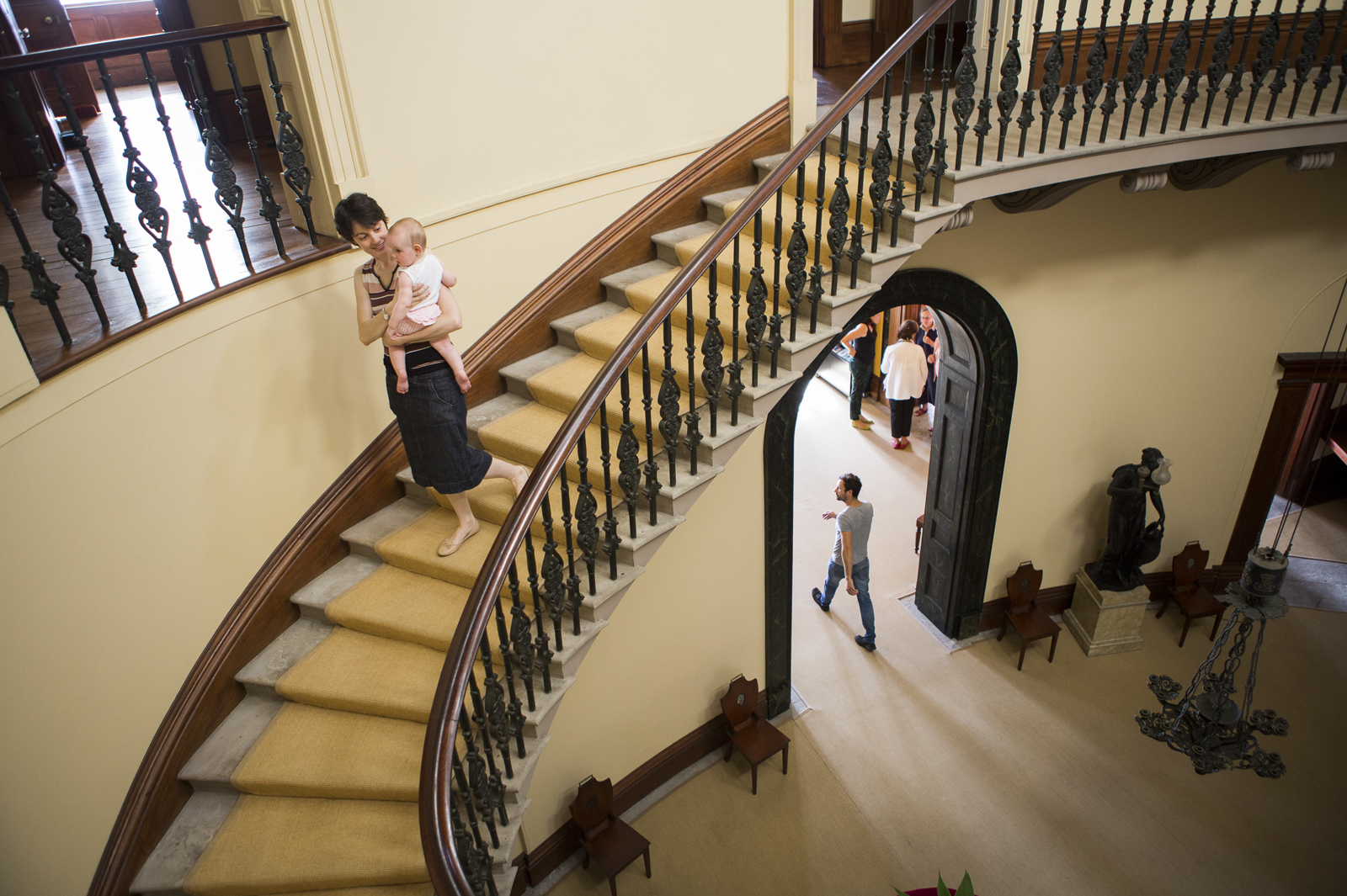 Woman and baby on the cantilevered staircase in the saloon, Elizabeth Bay House, with other visitors visible on the ground floor.