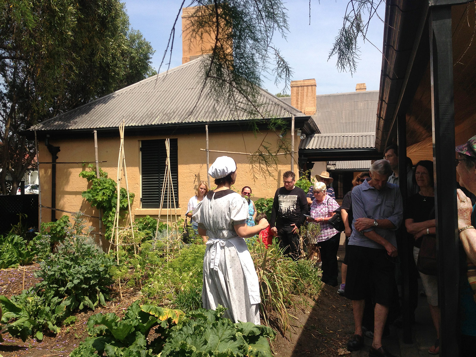 Female visitor services staff member dressed in period costume of servant, facing tour group while standing in garden bed.