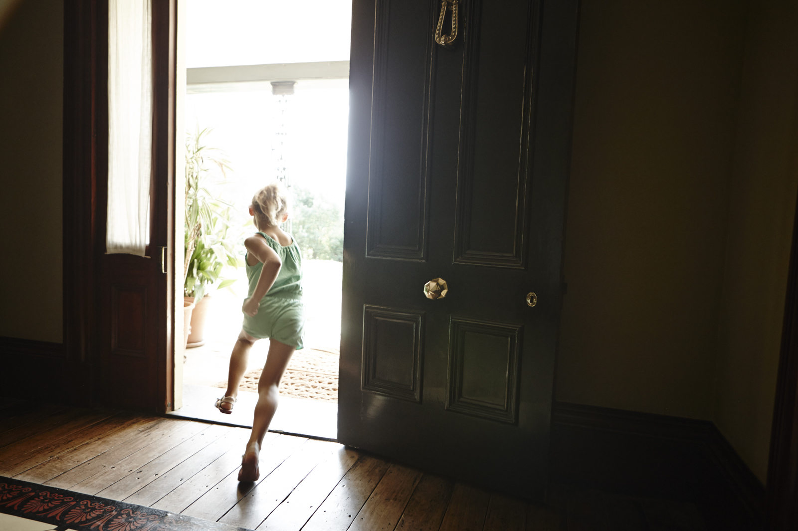 Girl running out of doorway into bright sunlight from dark room.