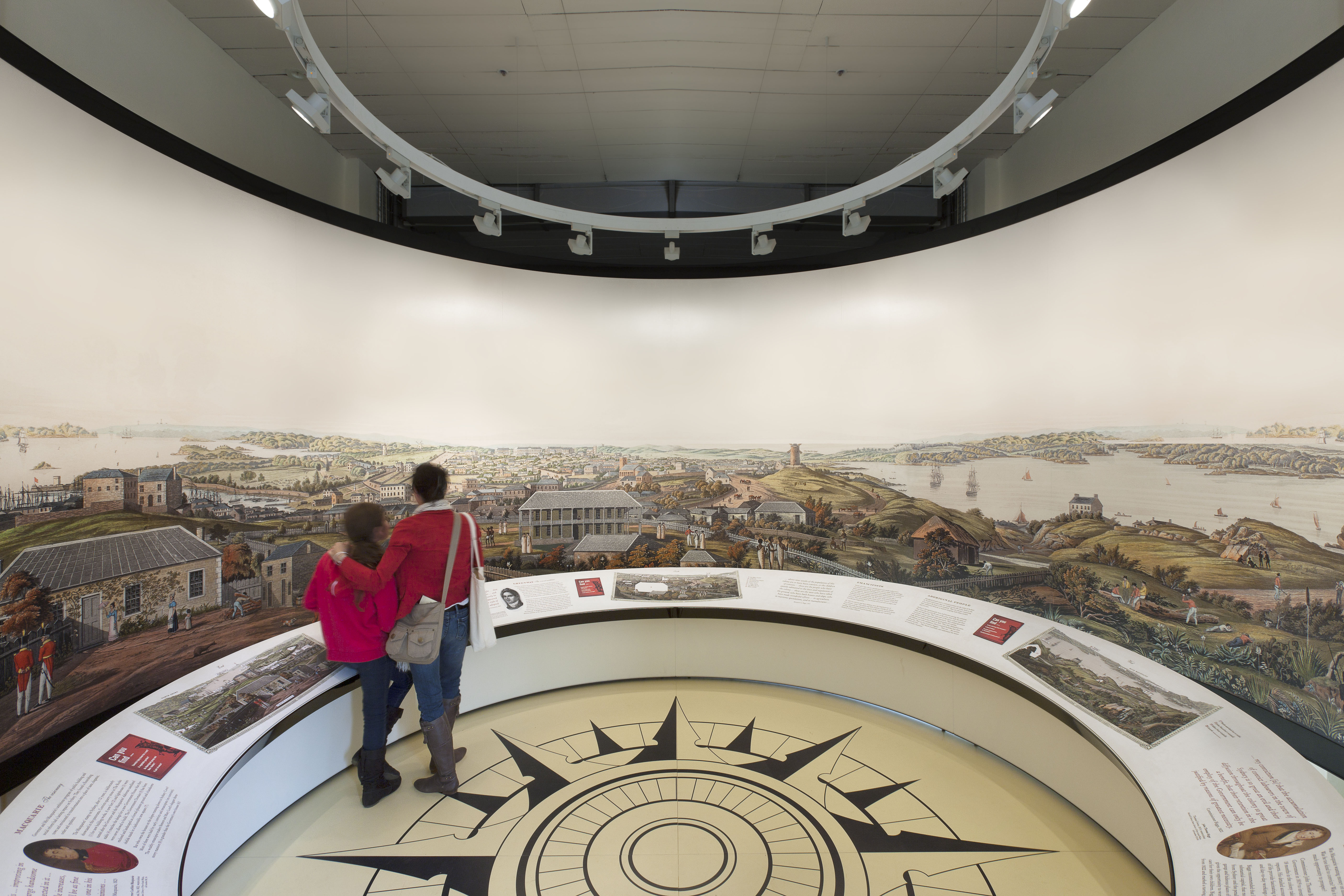 Two visitors standing in front of circular panorama installation in Convict Sydney exhibition. On the floor is a large compass graphic.