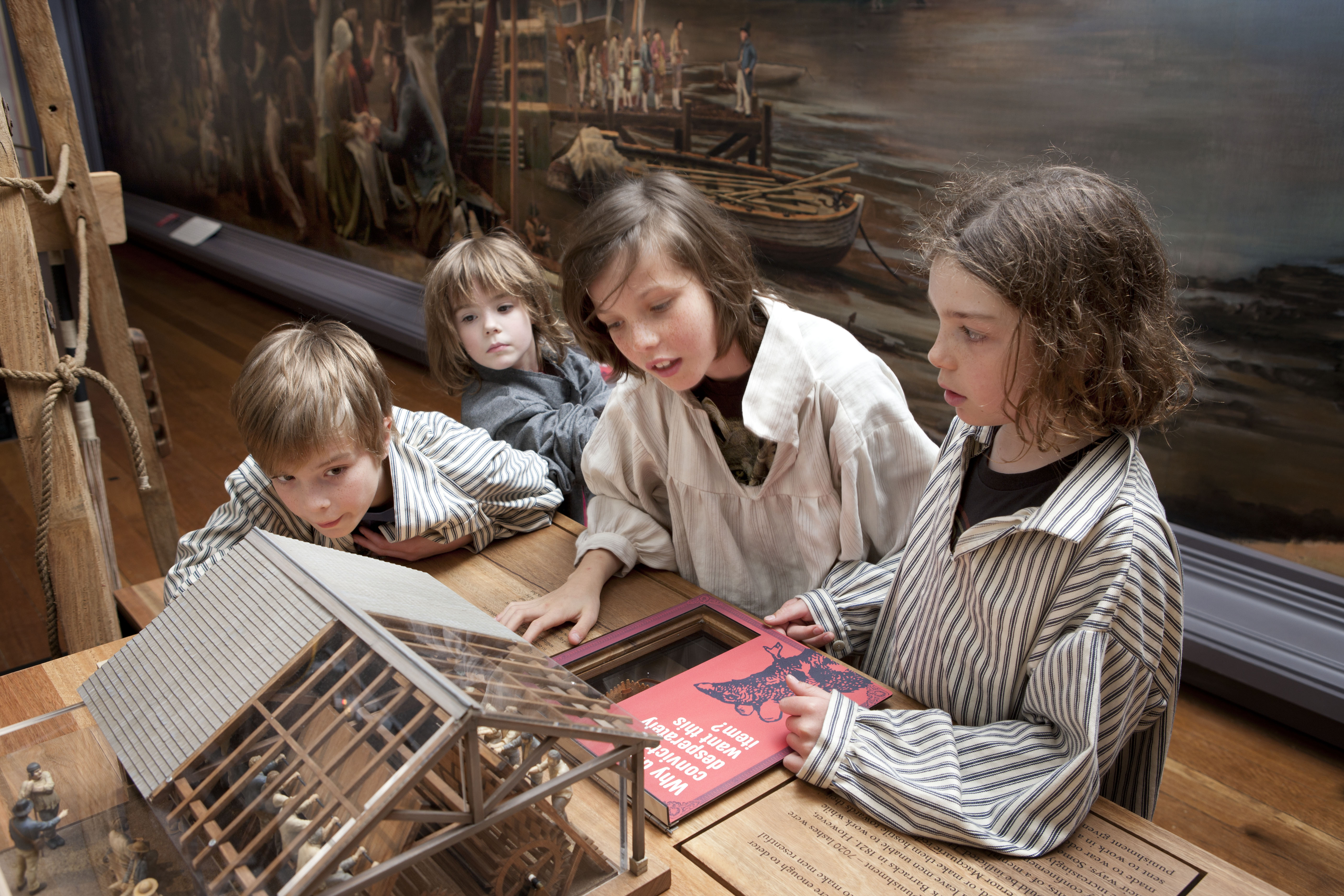 Four young visitors looking at the treadmill interactive in the Convict Sydney exhibition