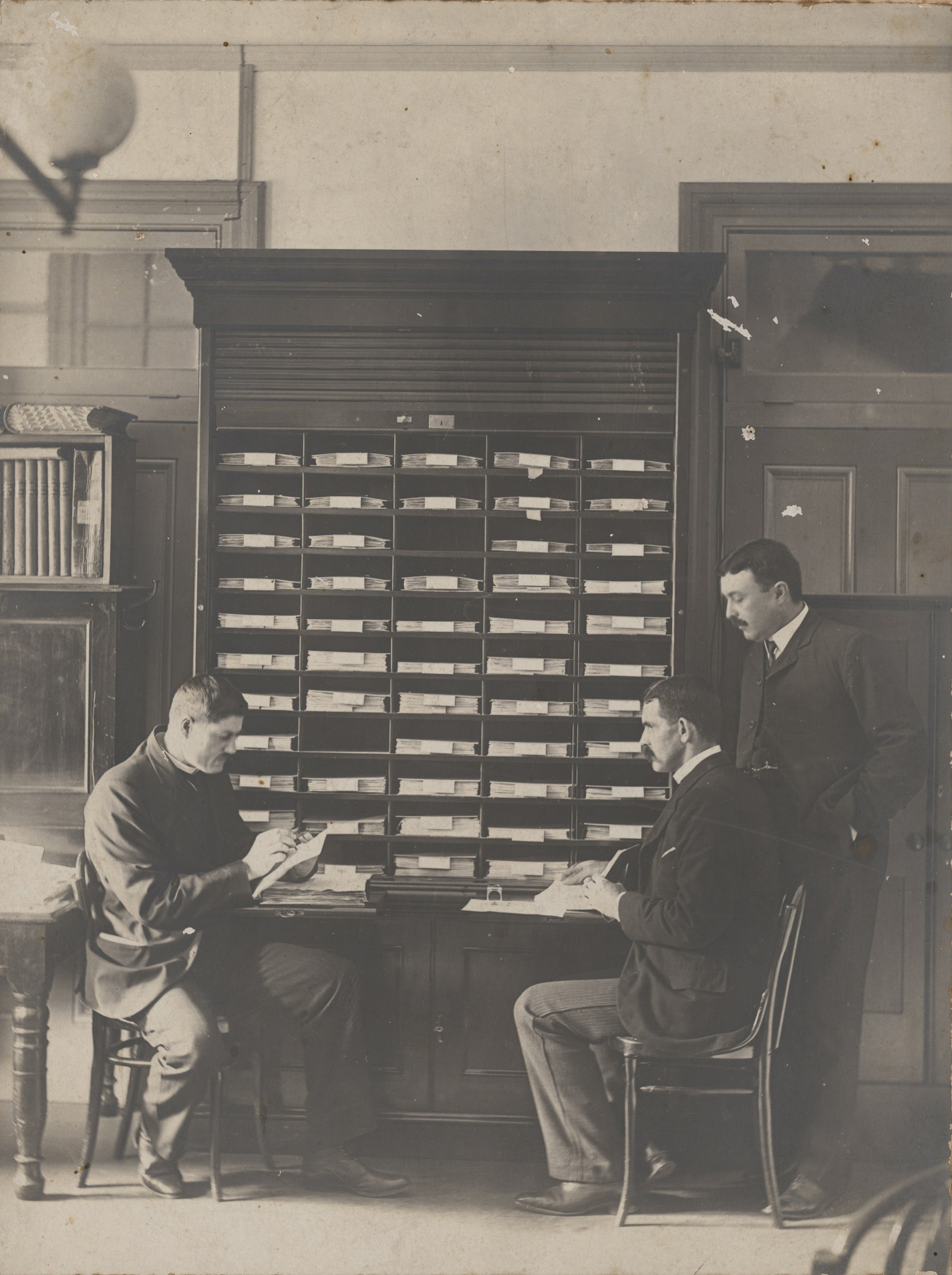 Men in front of tall cabinet of shelving, two seated at table, one standing.