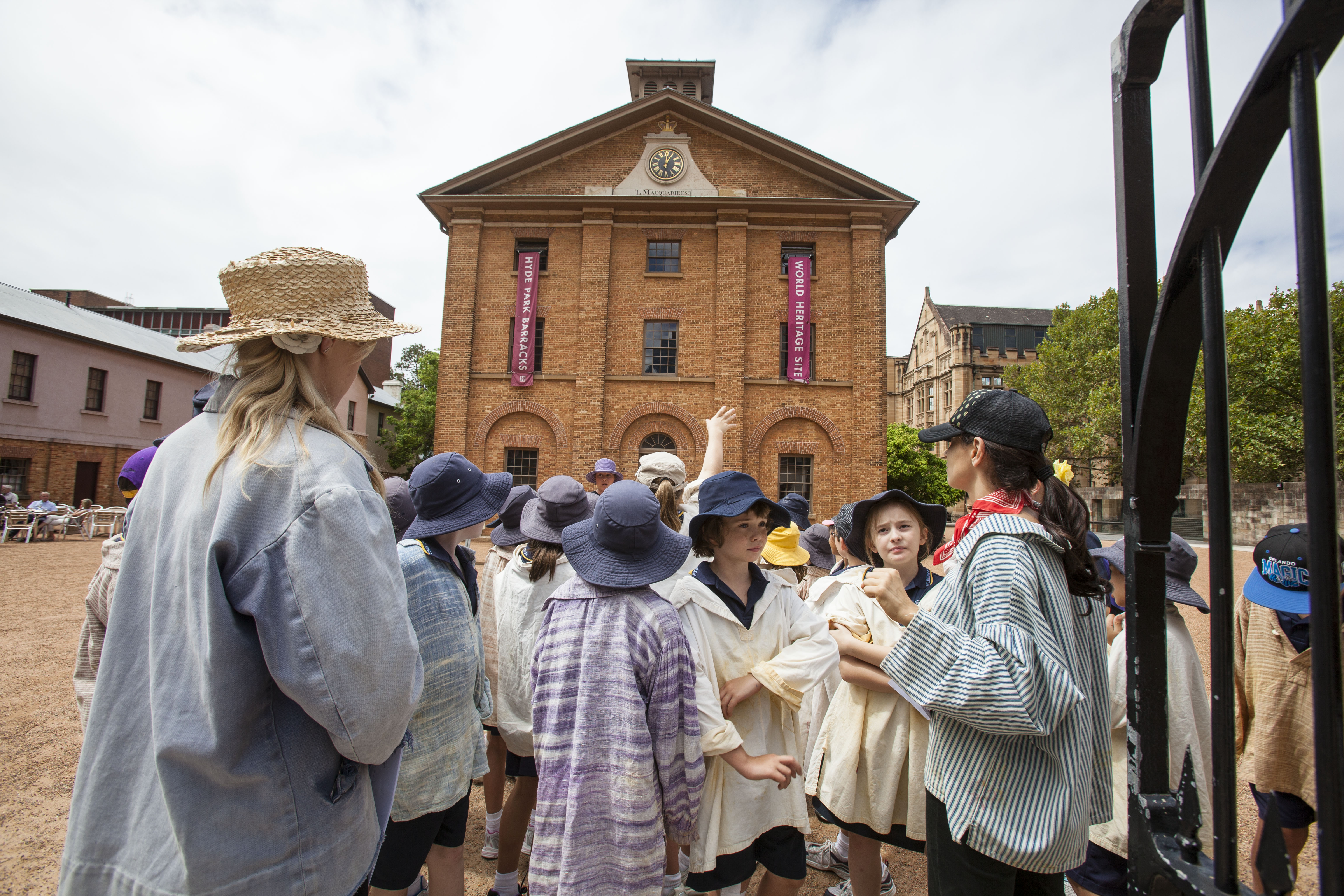 Students dressed as convicts standing at the Barracks gates. The main building can be seen behind them.