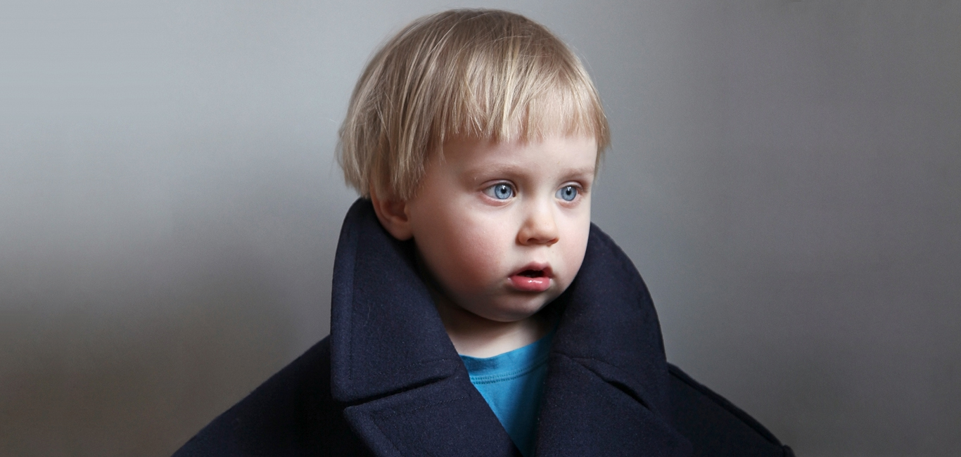 Pensive looking child photographed against blue background.