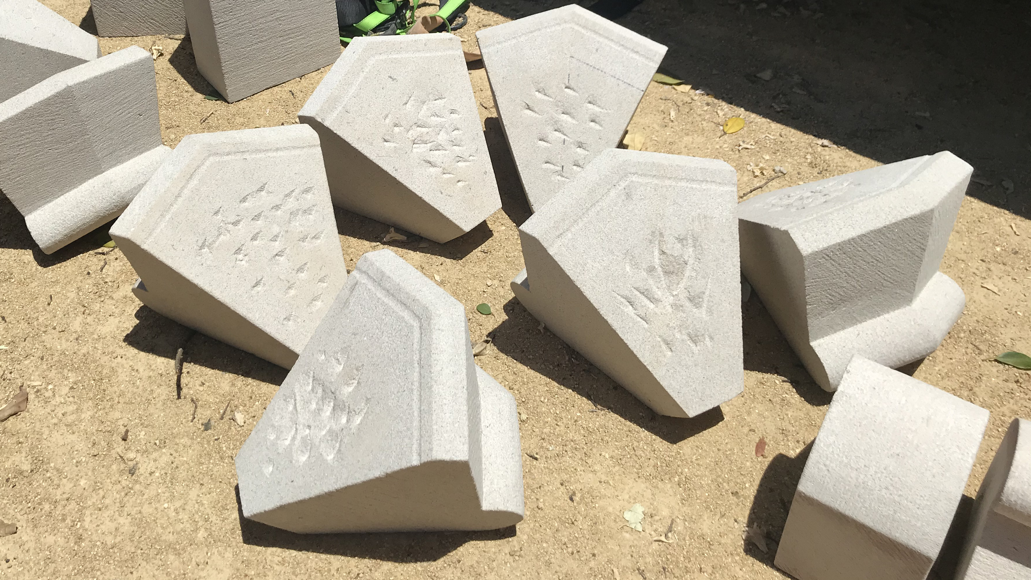 Pieces of cut and shaped sandstone on ground.