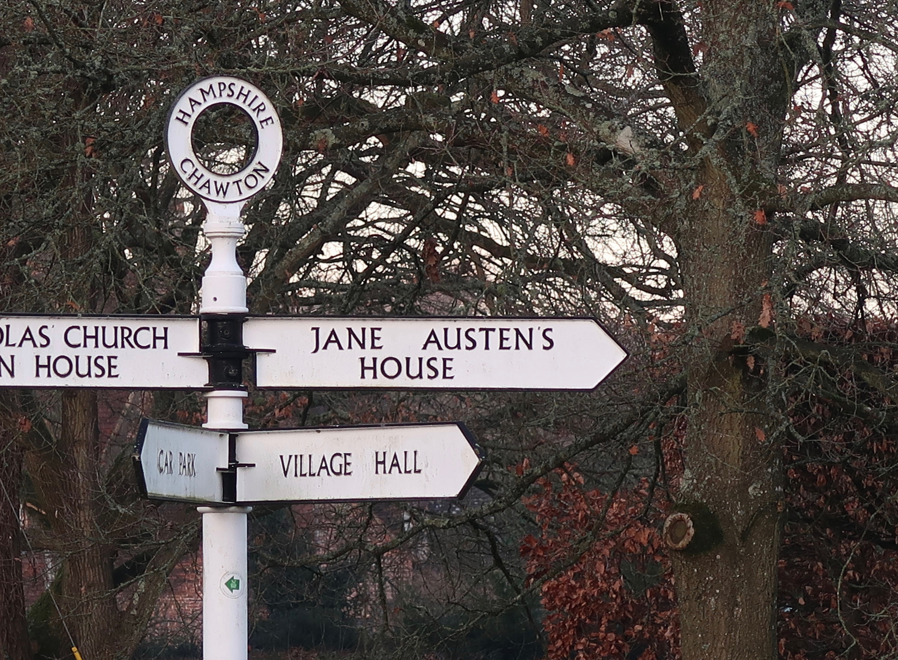 White signpost with several signs pointing in different directions.