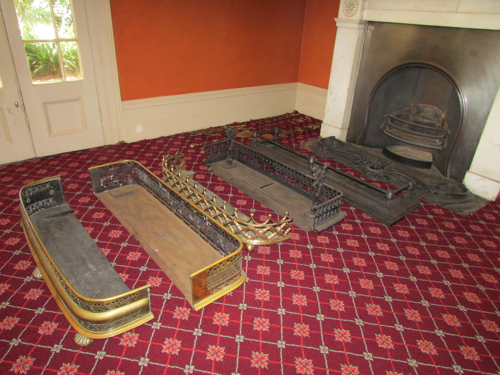 5 metal fenders of varying shapes on a red patterned carpet in front of a fireplace.