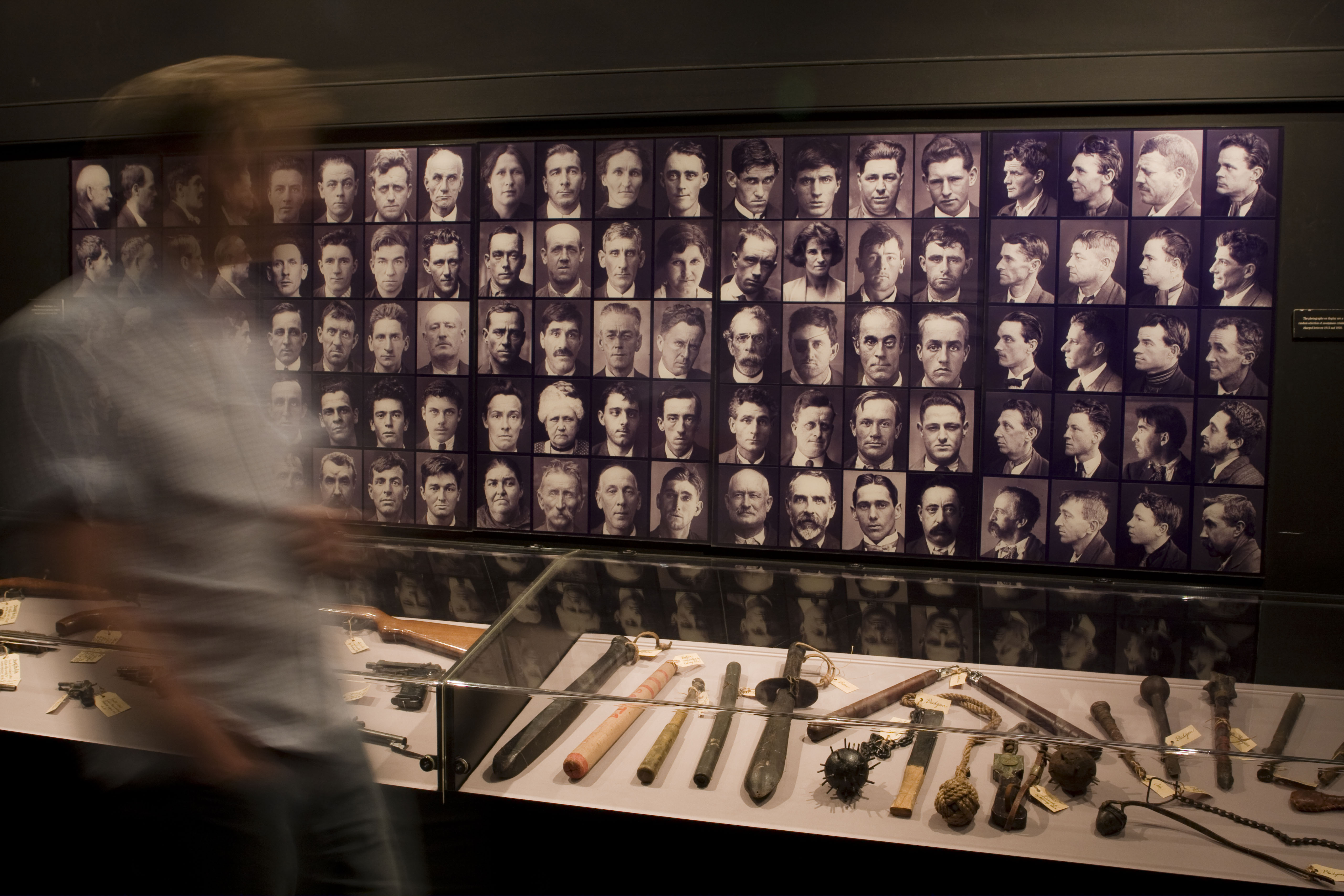 Photo showing person rushing past a photographic display of portraits and weapons under glass in a showcase.