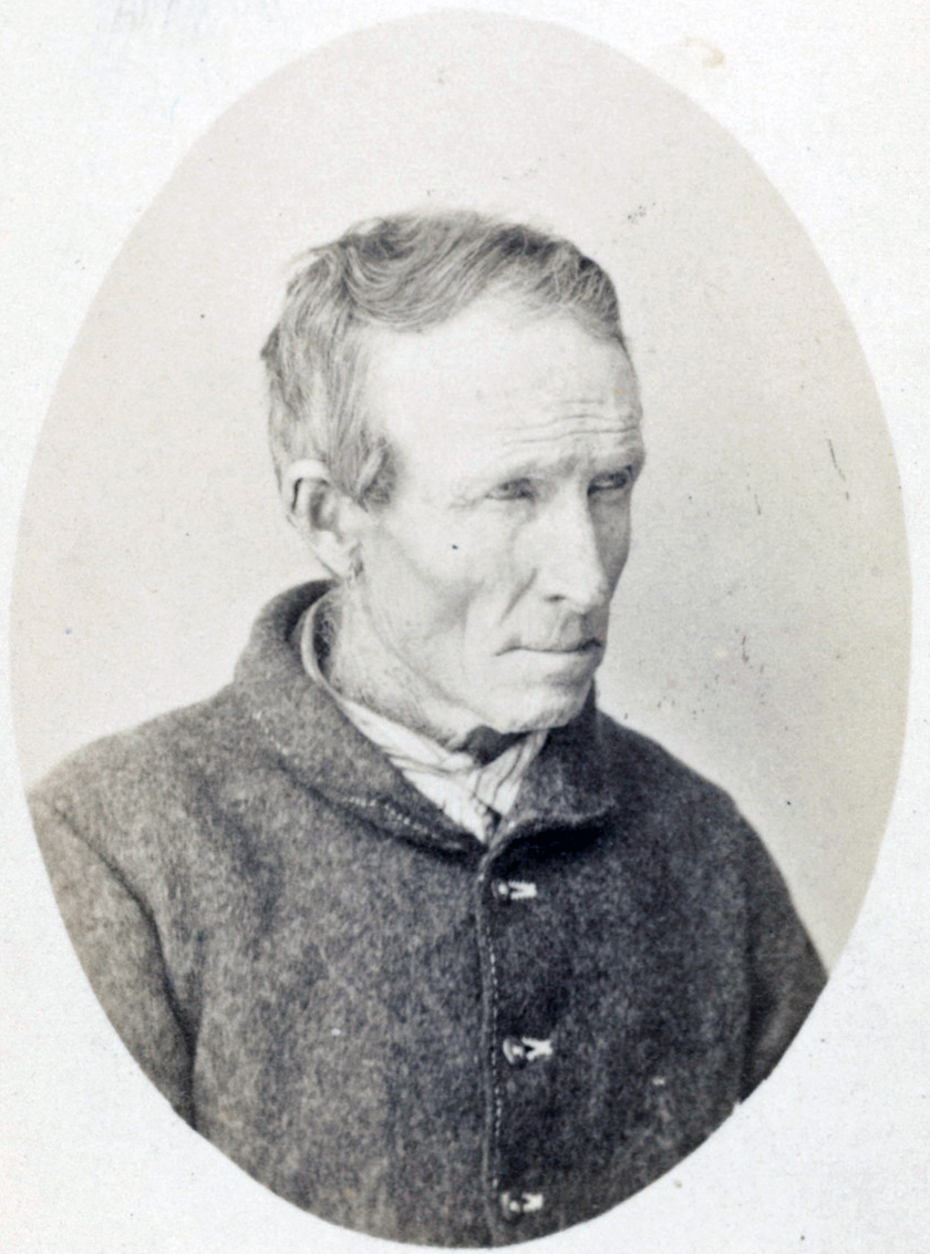 Black and white early photograph of man with bare head.