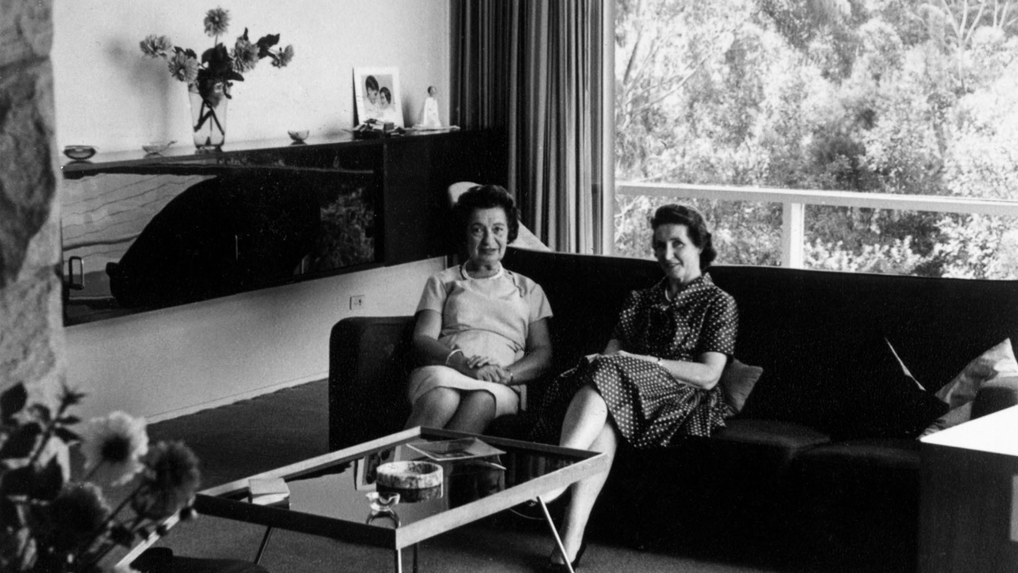 Black and white photo of two women seated on sofa.