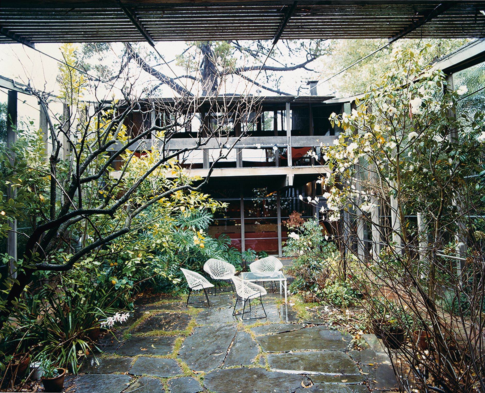 This is a colour photograph of a courtyard with large stone paving, a white metal table and chair setting, and surrounded by flowering shrubs and trees