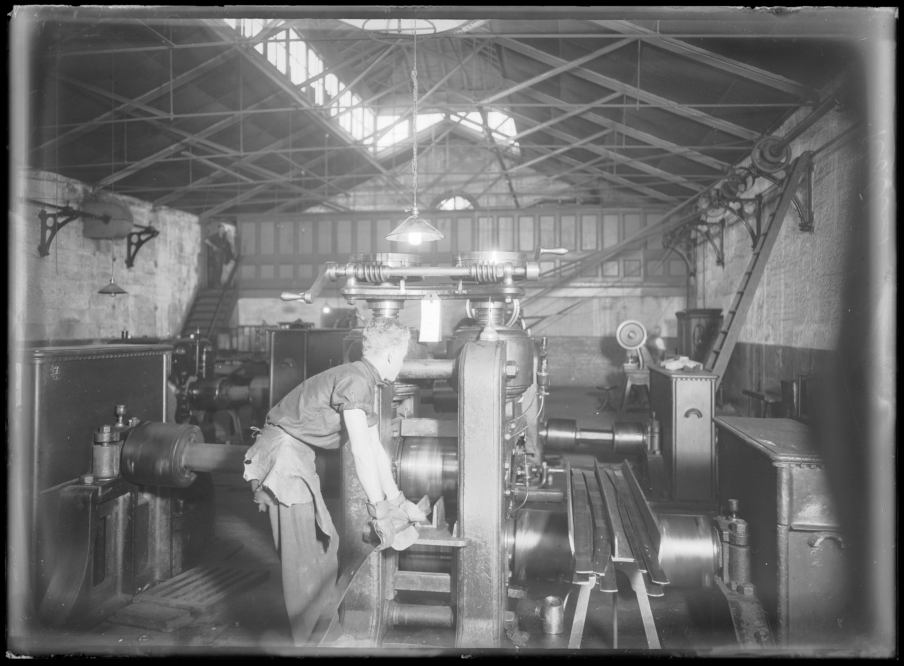 Black and white photo of a man working a coin press