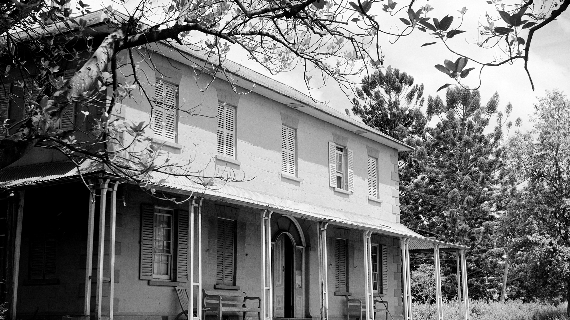 Facade of two storey house with shaded verandah on ground level.