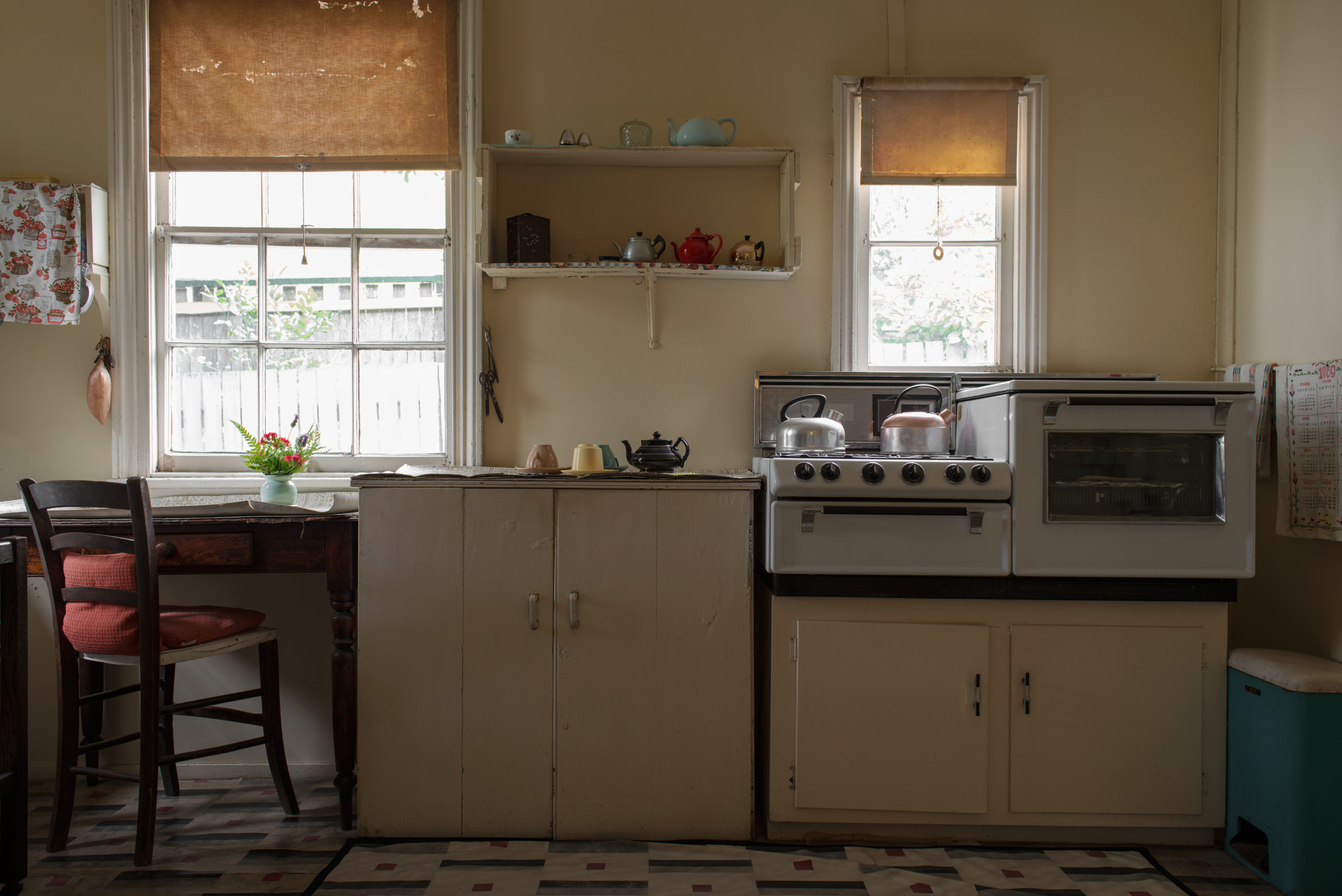 Benchtop and cupboards below curtained windows in older style kitchen.