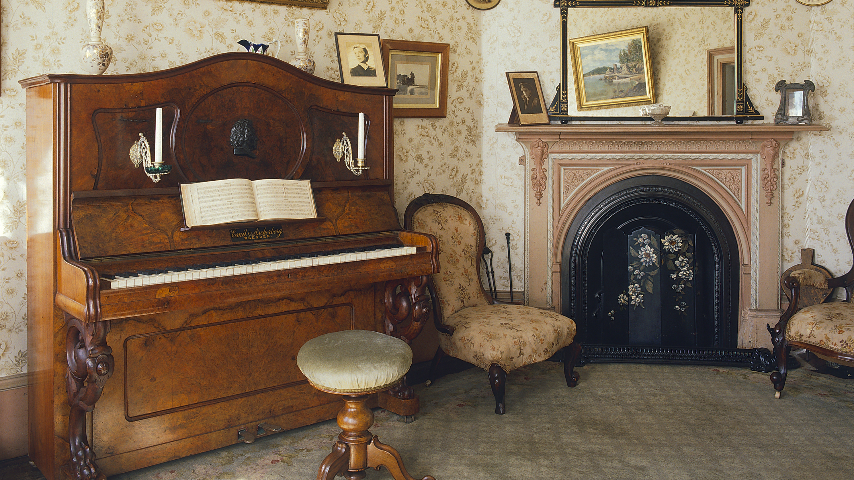 Piano in wallpapered room to left of fireplace flanked by chairs.