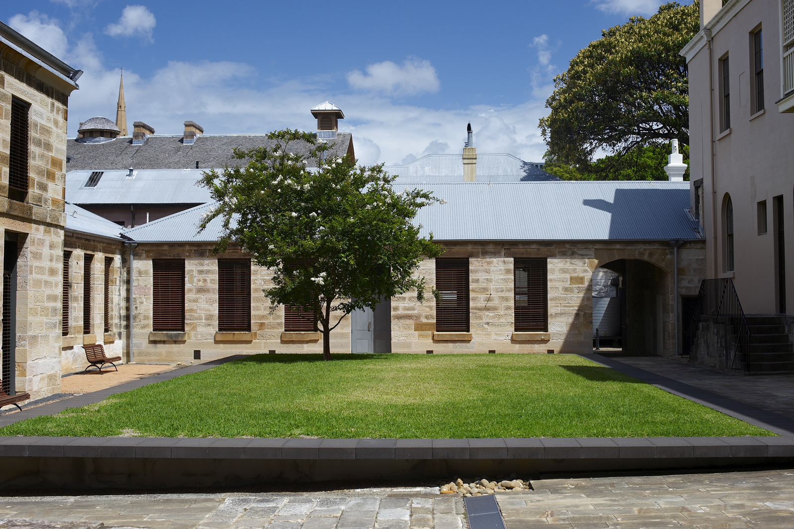Rectangular green lawn with tree, bounded by low stone wall, in centre of stone paved courtyard, surrounded by three out of the four wings of the Mint buildings.