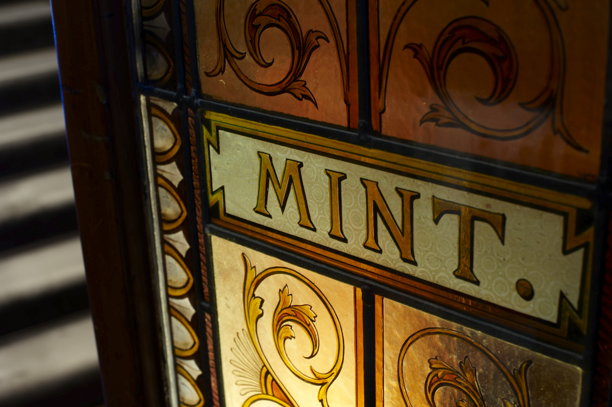 A decorative glass door panel with the word 'Mint' painted onto it in gold lettering.