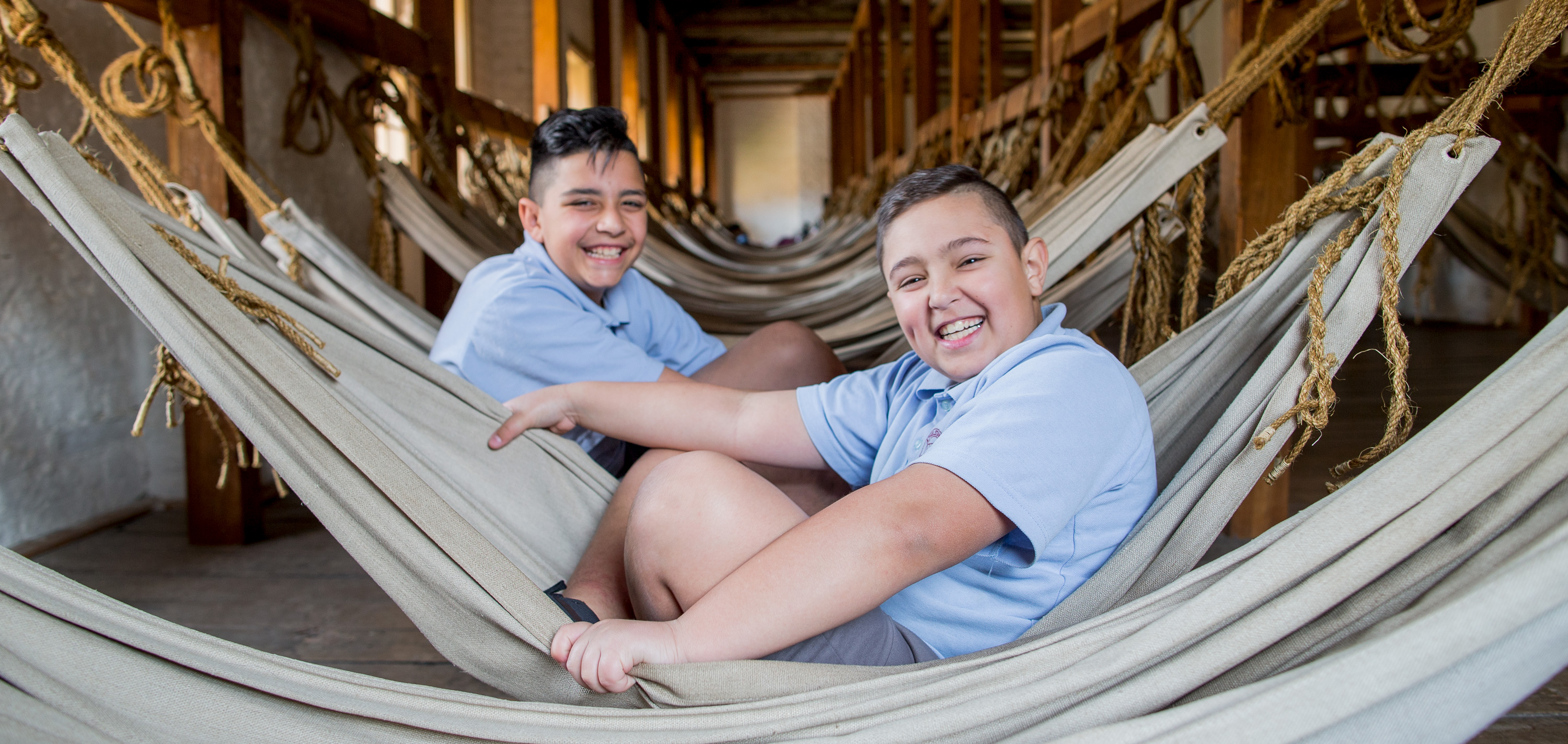 Two smiling kids in hammocks