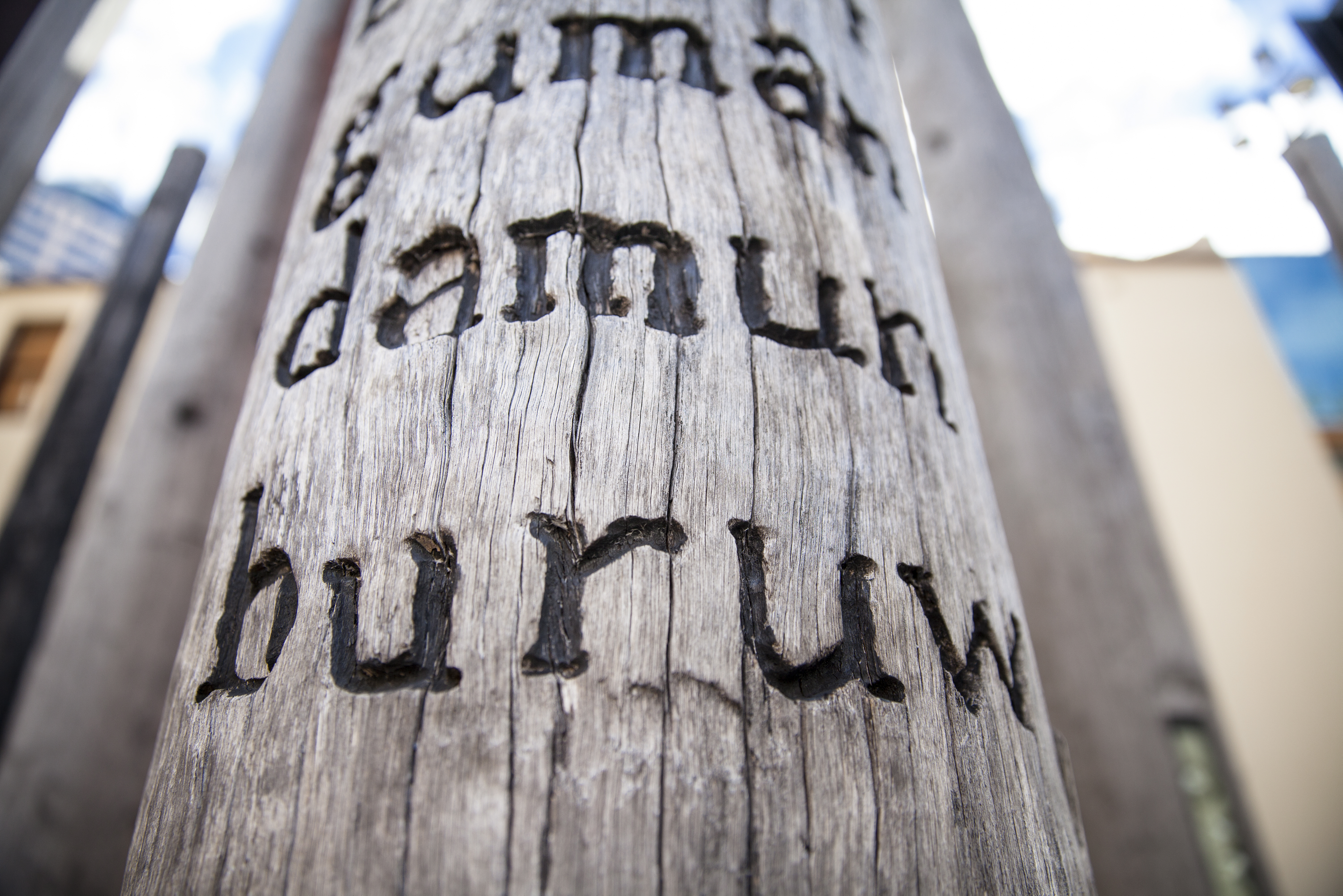 Gadigal words burnt in timber post for public artwork.
