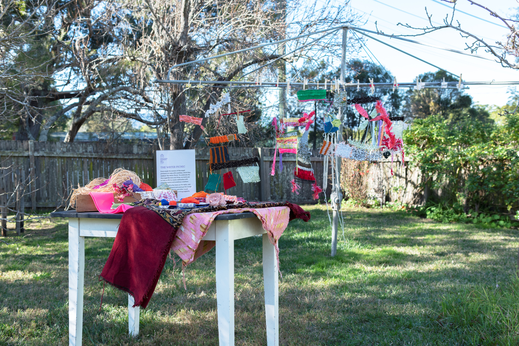 Clothesline with artworks hanging from it, with table in foreground with art supplies.