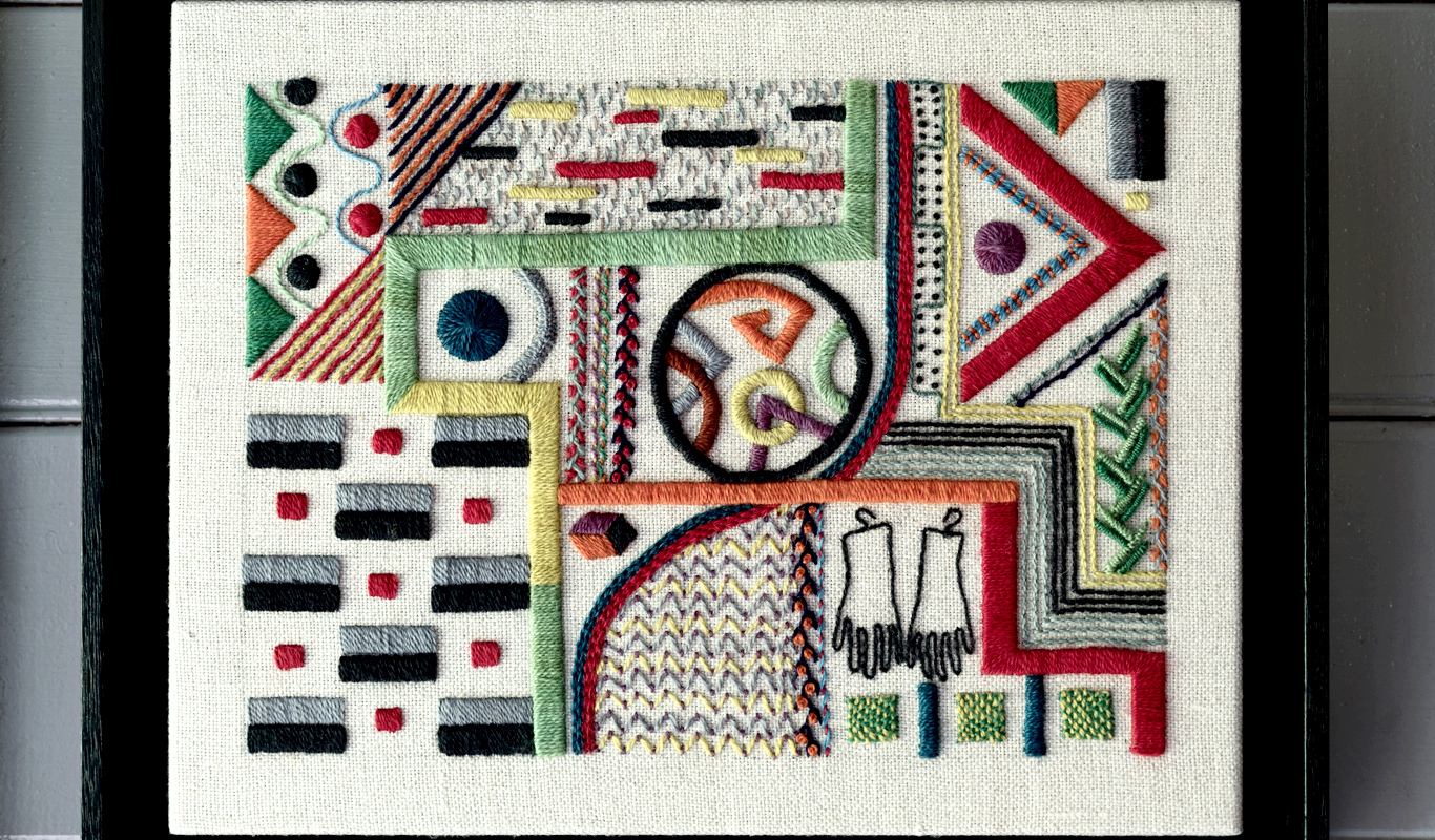 Framed piece of embroidery with geometric and other motifs.