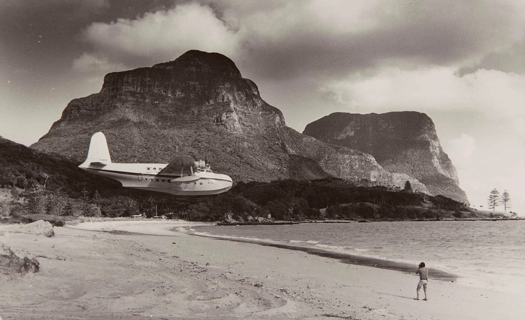 Flying boat comes in to land low over a beach heading for the water below the peak of Lord Howe Island in the background