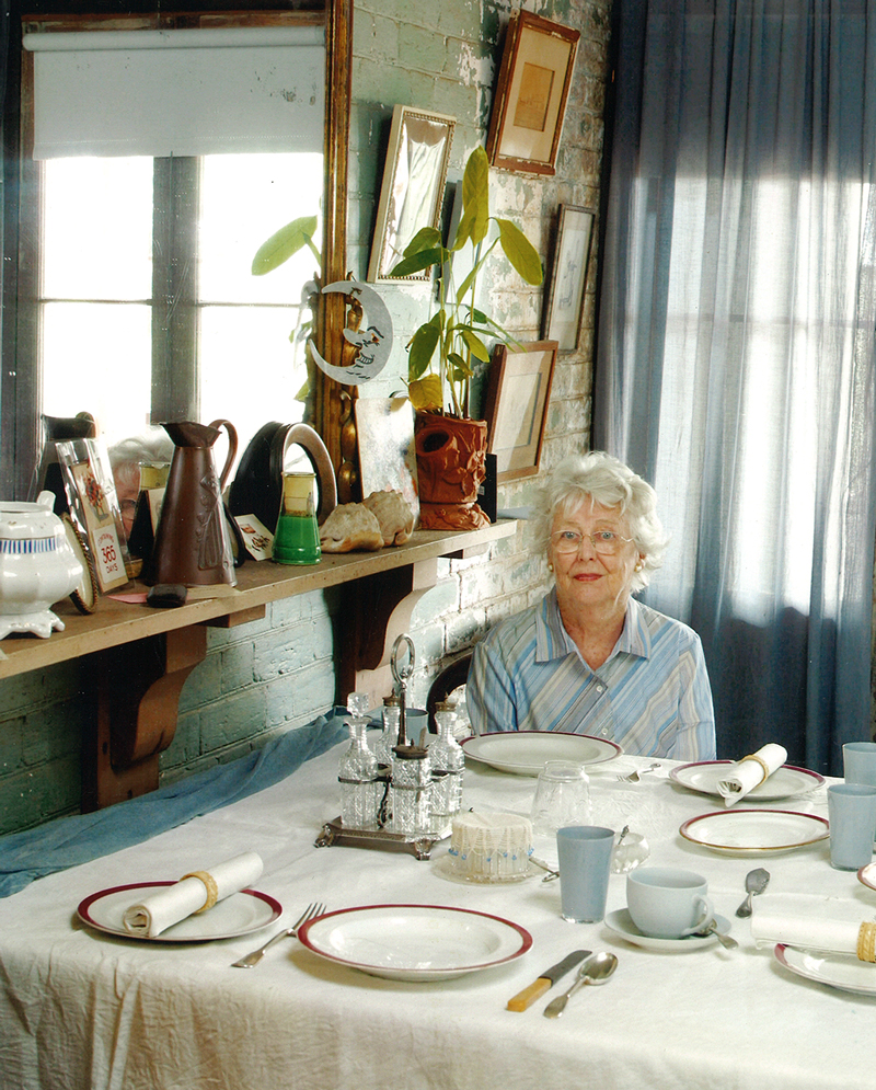 White haired lady seated at table set for a meal, with window in background.