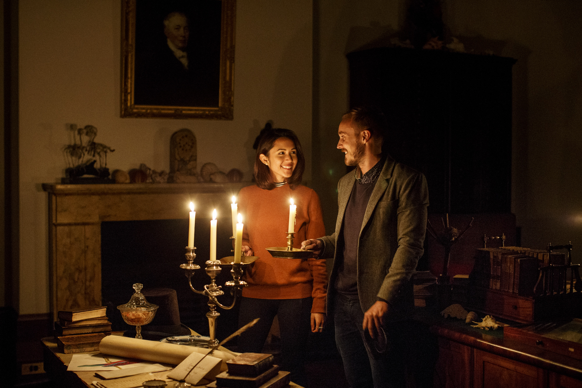 Man and woman in darkened room with candles lighting space.