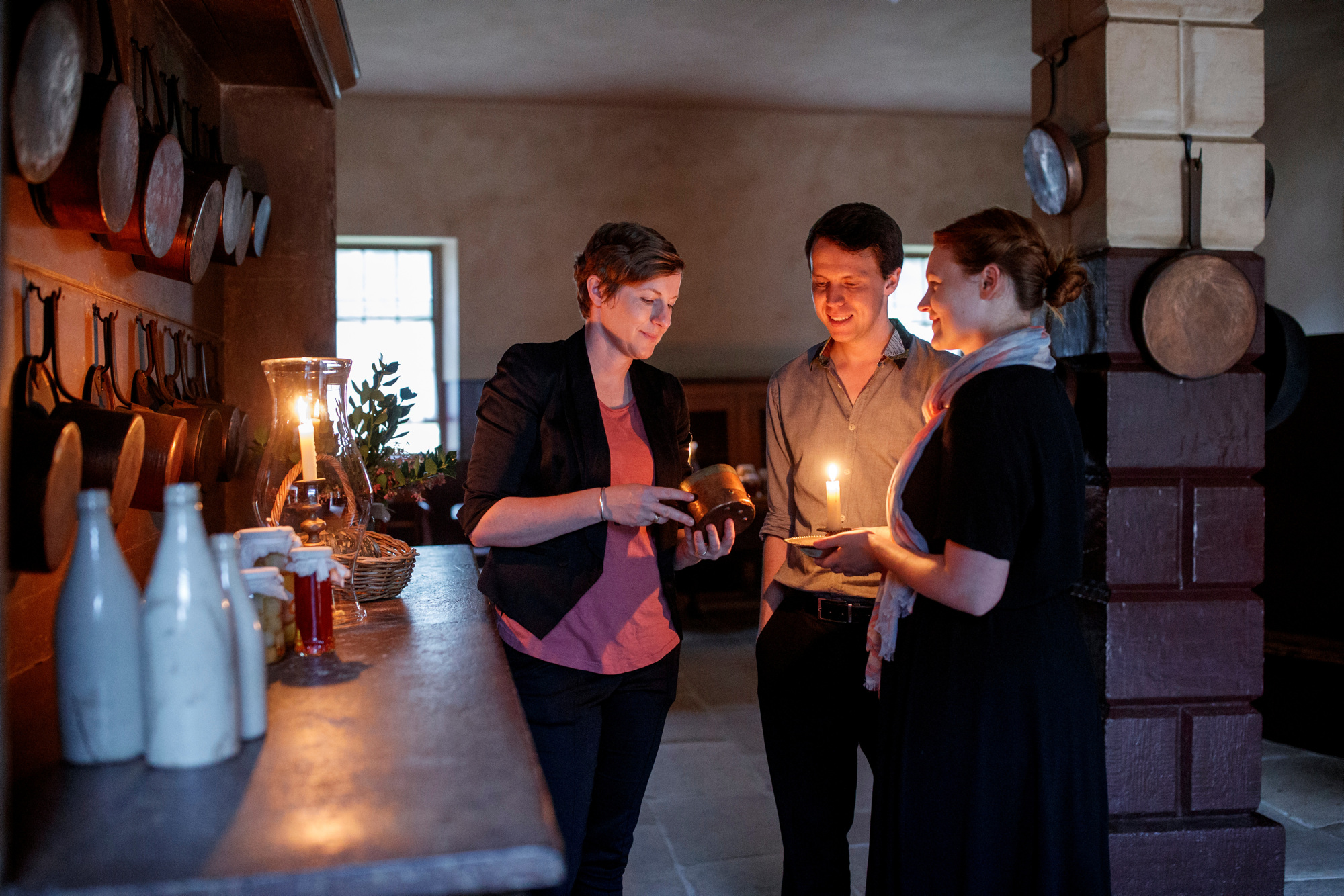 Woman guiding man and woman through kitchen by candlelight.
