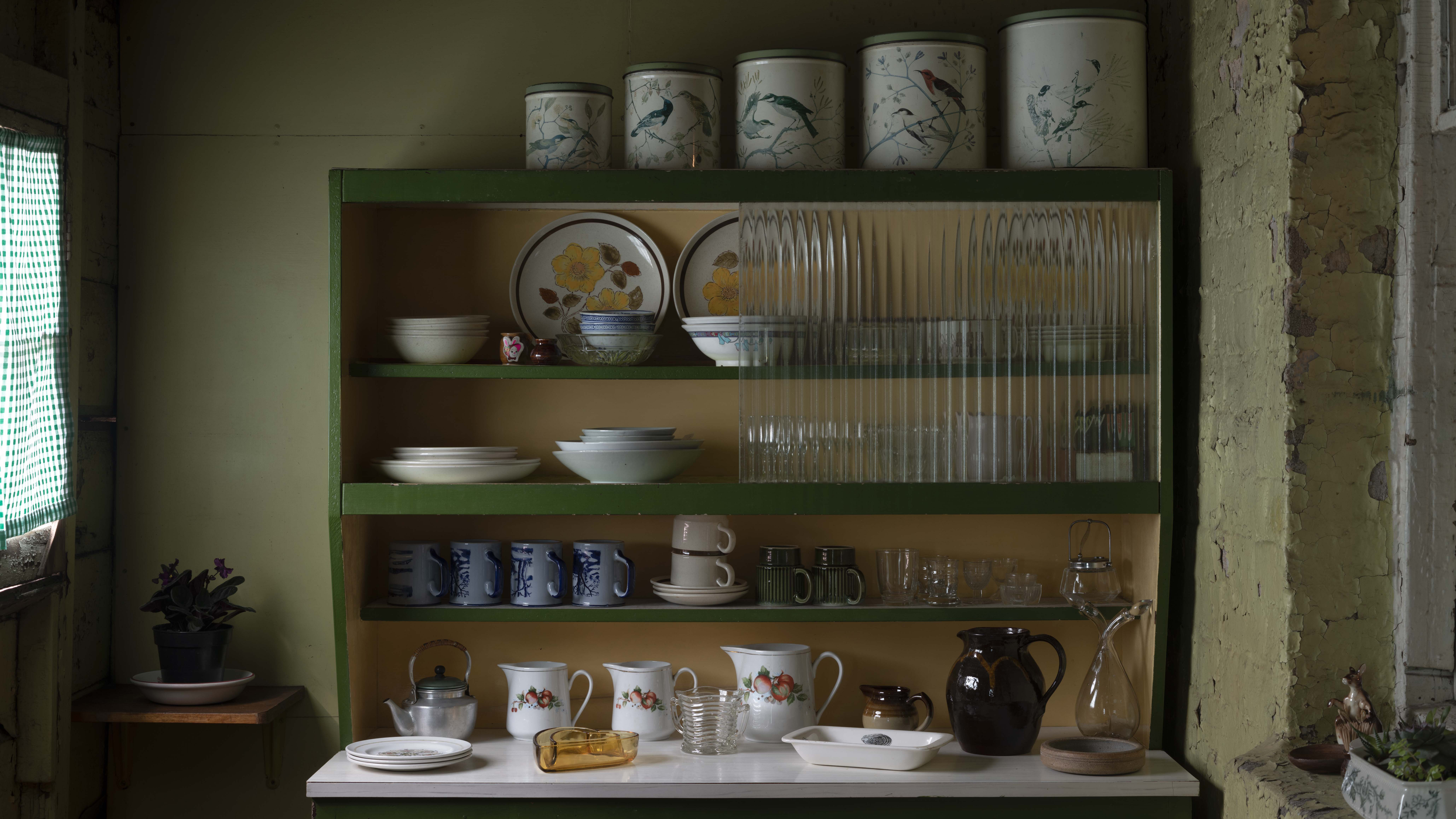 Dresser with array of tins, crockery and other kitchen items, lit by gingham-curtained window on left of photo.