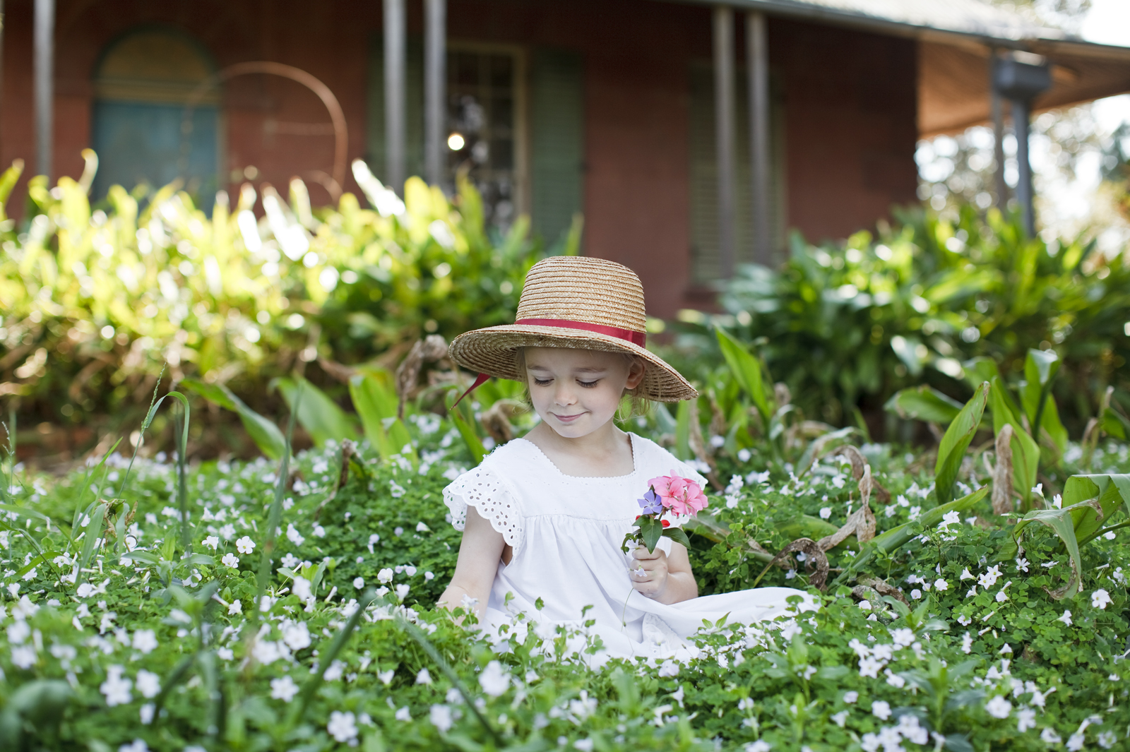Small girl in garden bed with flowers outside main house.