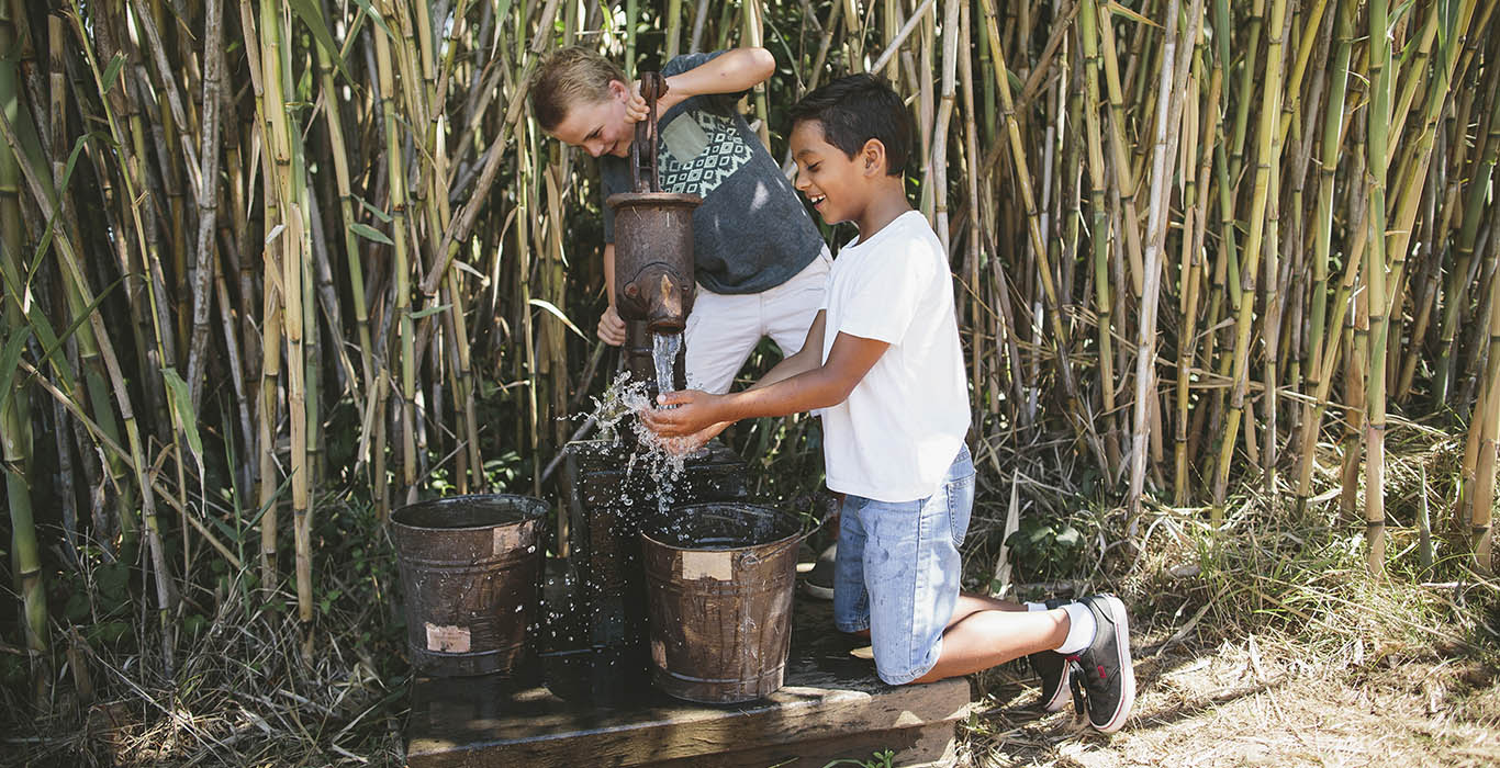 Two young boys pump water