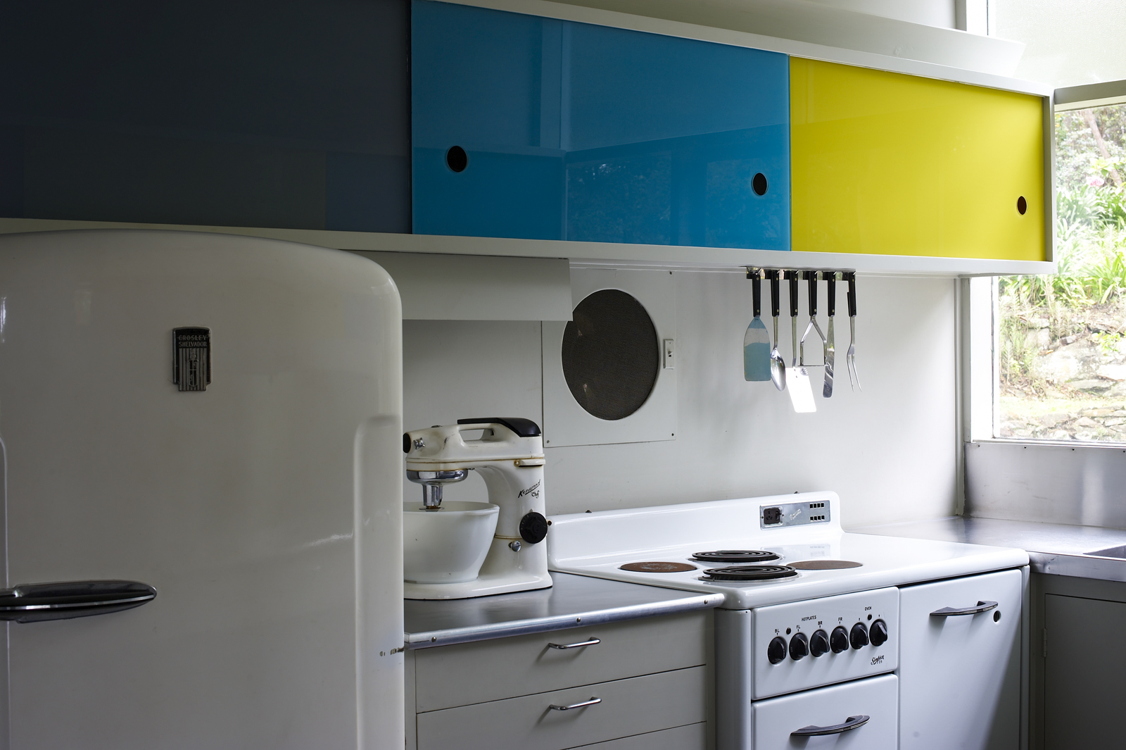 View of the kitchen showing the refrigerator, bench top and kitchen cupboards done in bold primary colours