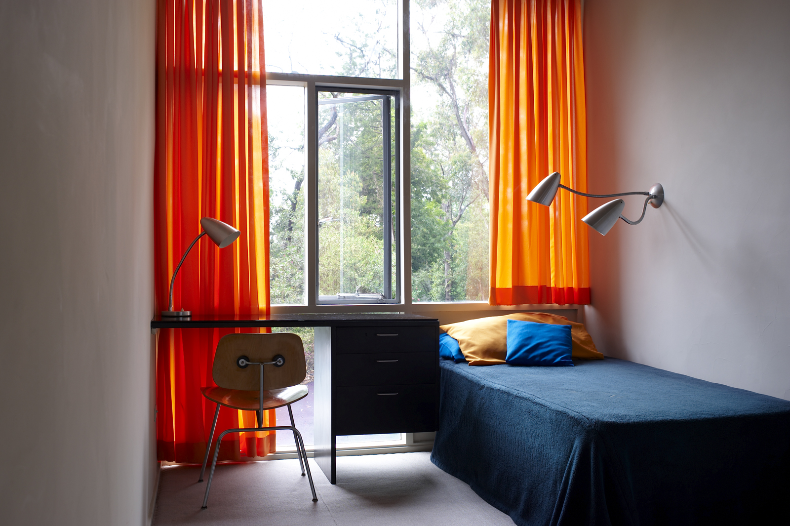View of child's bedroom, Rose Seidler House, showing desk, chair, lamps, single bed and orange curtains.