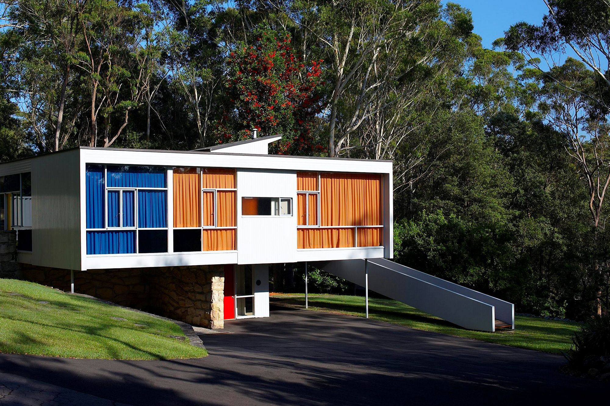 Rectangular modernist house set in garden with trees behind and long white ramp to right of building leading up to side entrance. Front door is underneath house.