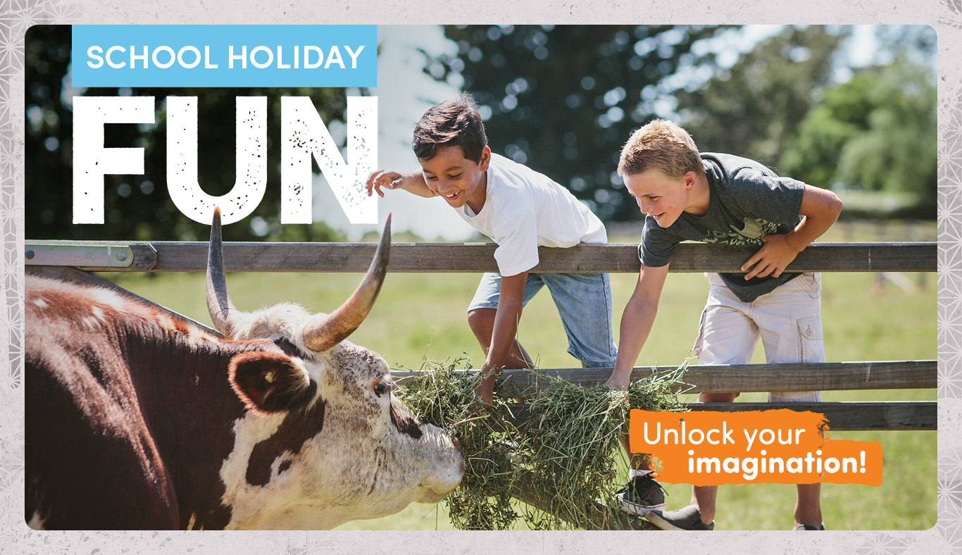 School Holiday Fun image of two kids feeding cow.