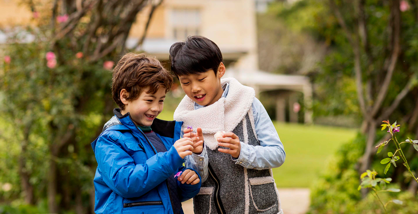 Promo image for school holiday programs with kids dressed in warm gear in outdoor setting.