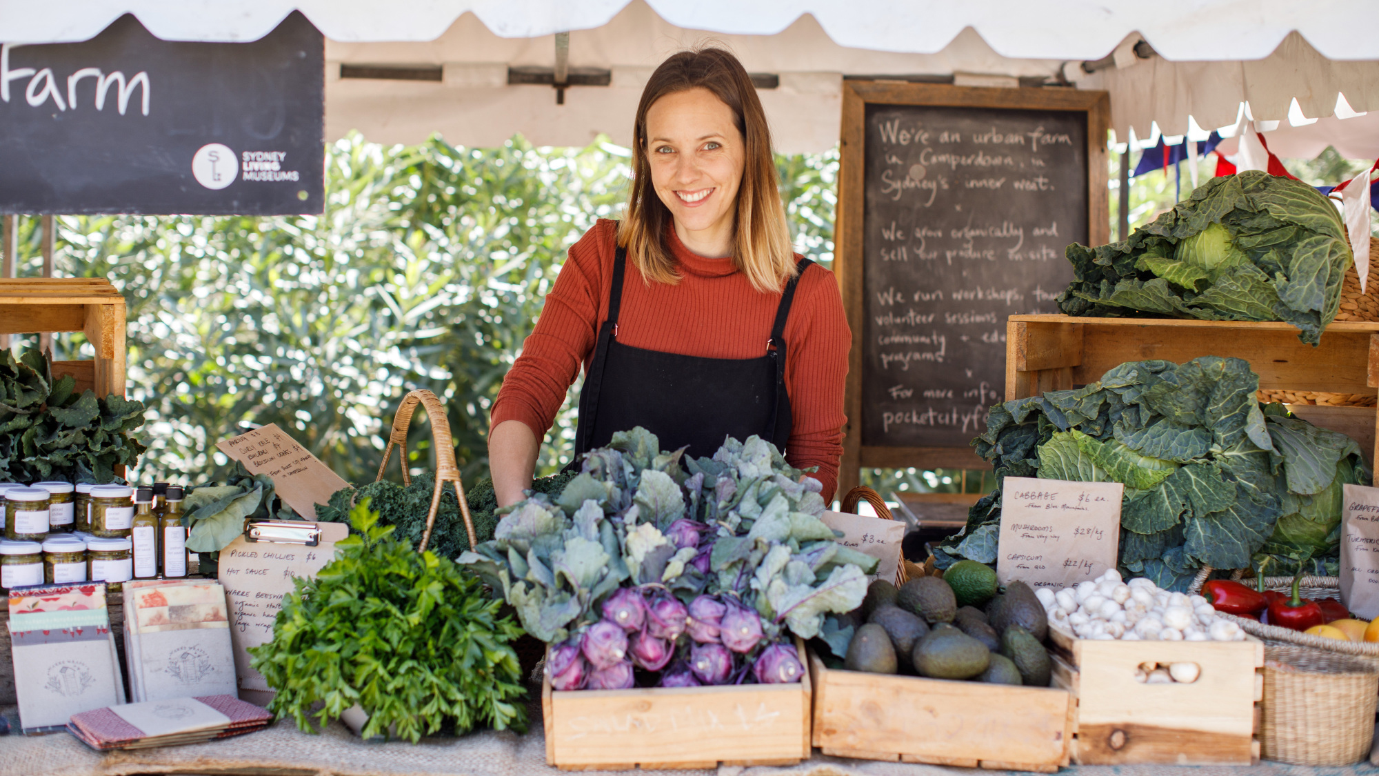 Woman at stall with fresh vegetables and other produce.