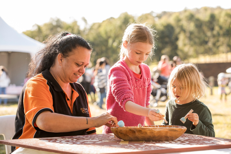 Woman and two girls doing activity at table outdoors.