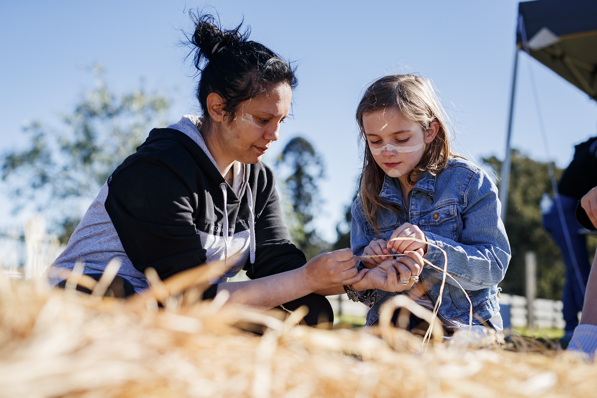 Woman showing child how to weave in outdoor setting, with weaving material in foreground.