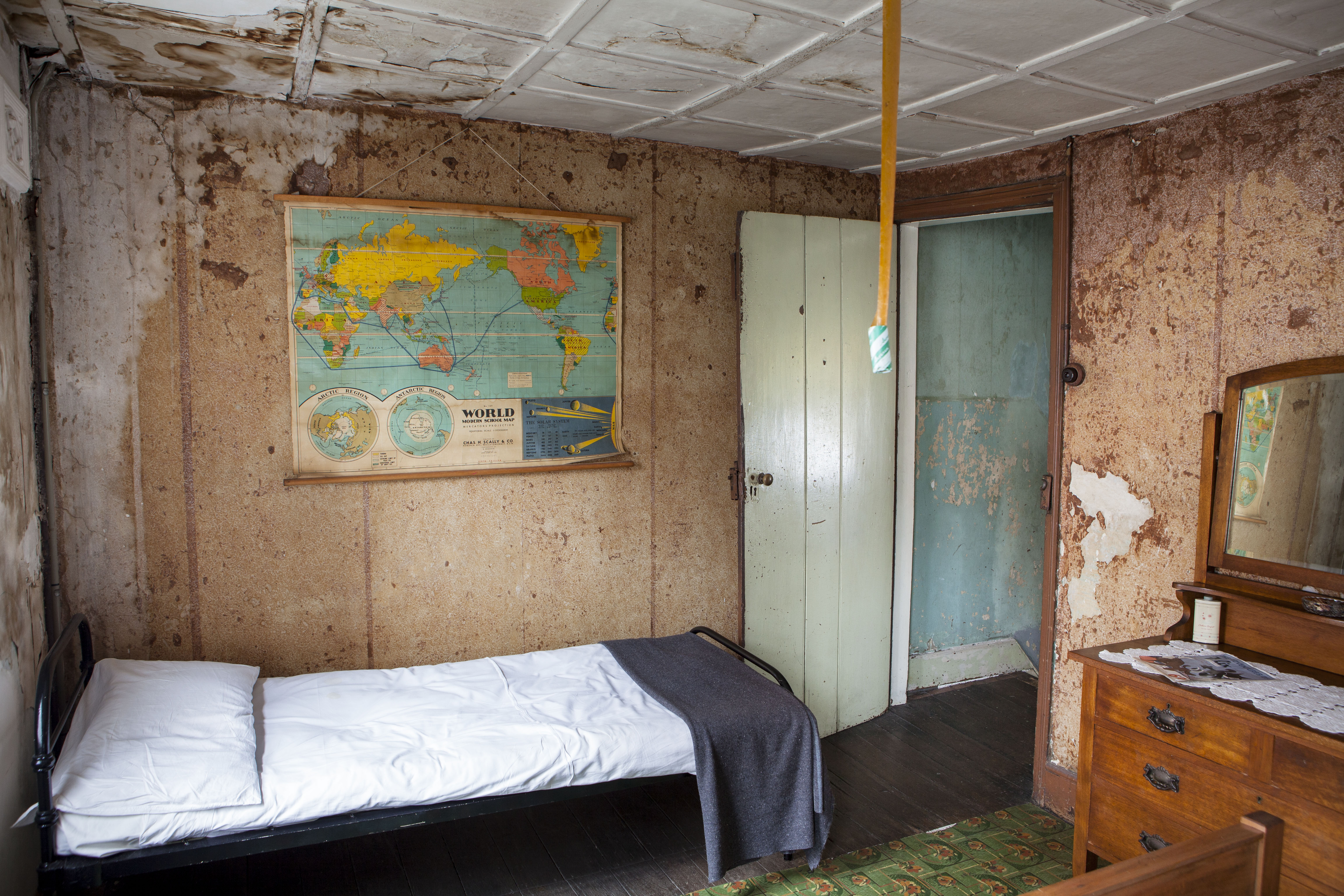 View of a bedroom with faded and torn wallpaper with an old map of the world on one wall, a single bed, dressing table and view through a door to the top of a staircase, with faded and damaged paintwork.